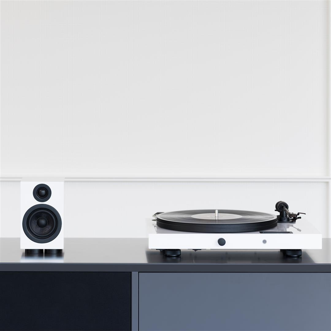 Pro-ject Juke box E white on table near single speaker