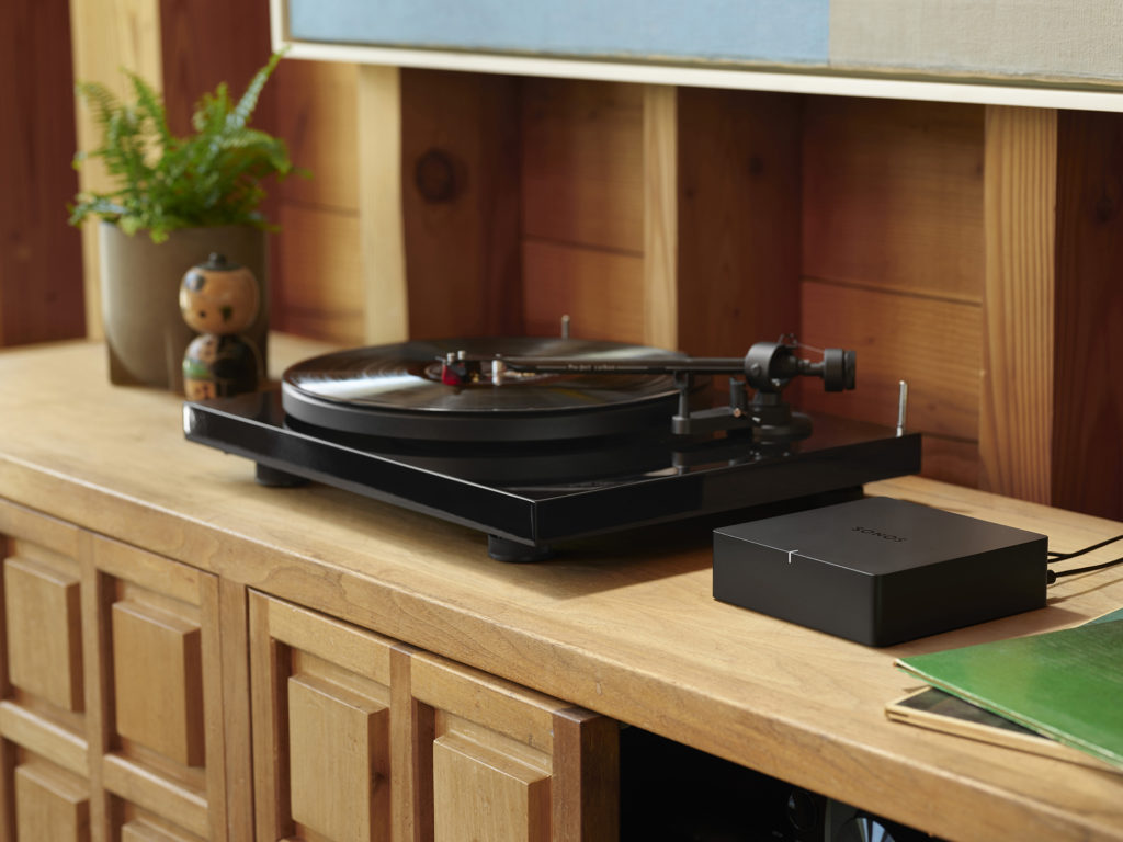 Sonos Port sitting on table beside turntable