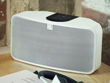 Bluesound Pulse mini on light wooden table lifestyle menu image