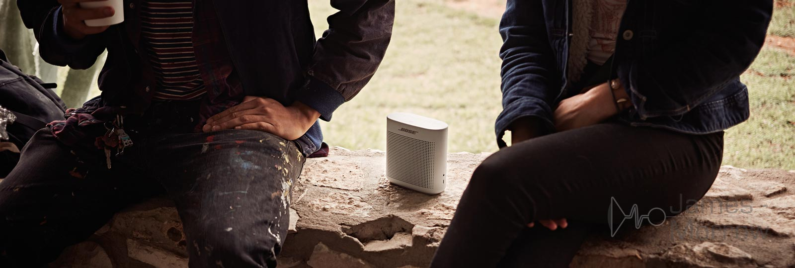 Bose SoundLink Colour II white on ground with two people lifestyle image