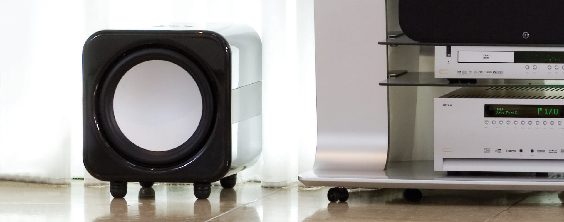 monitor audio apex aw12 subwoofer on floor near stand lifestyle banner image