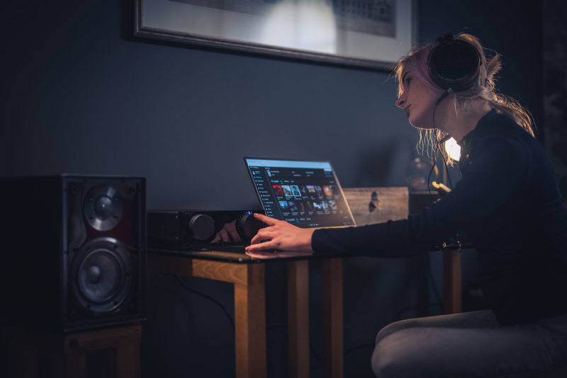 Woman on laptop using Cyrus One Linear with headphones