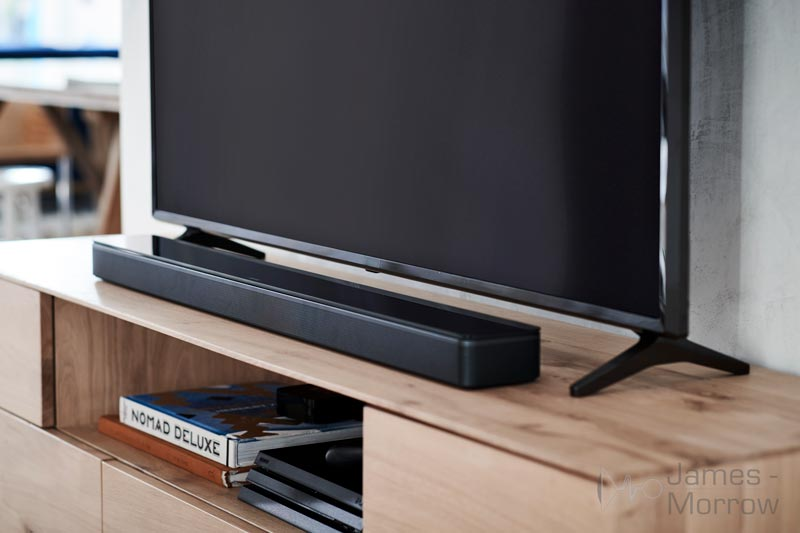 Bose Soundbar 700 black on wooden table under TV lifestyle image