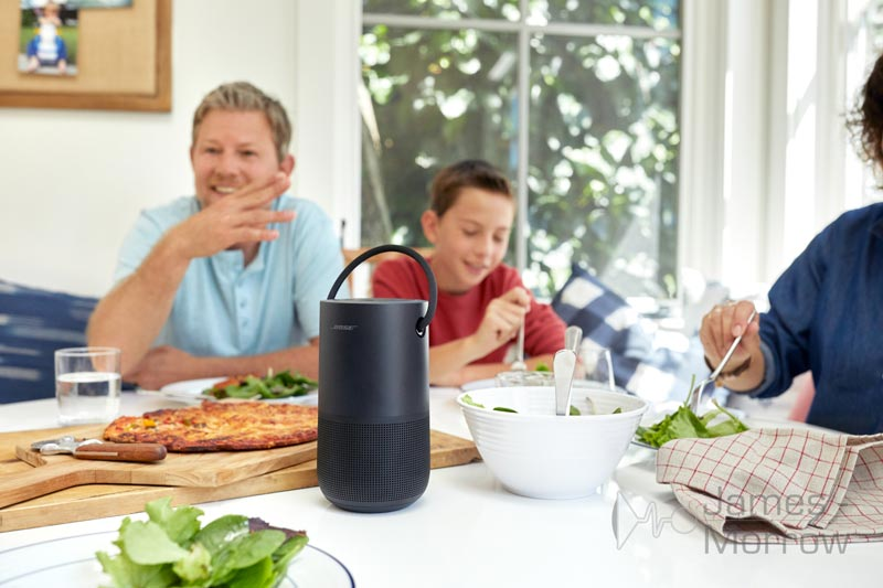 bose portable home speaker black on kitchen table with family lifestyle image
