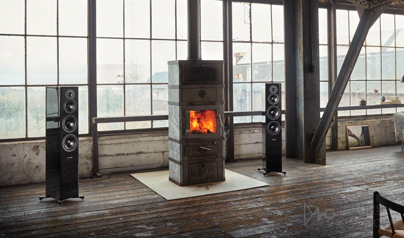 Dynaudio Evoke 50 Black speakers near lit fireplace lifestyle image