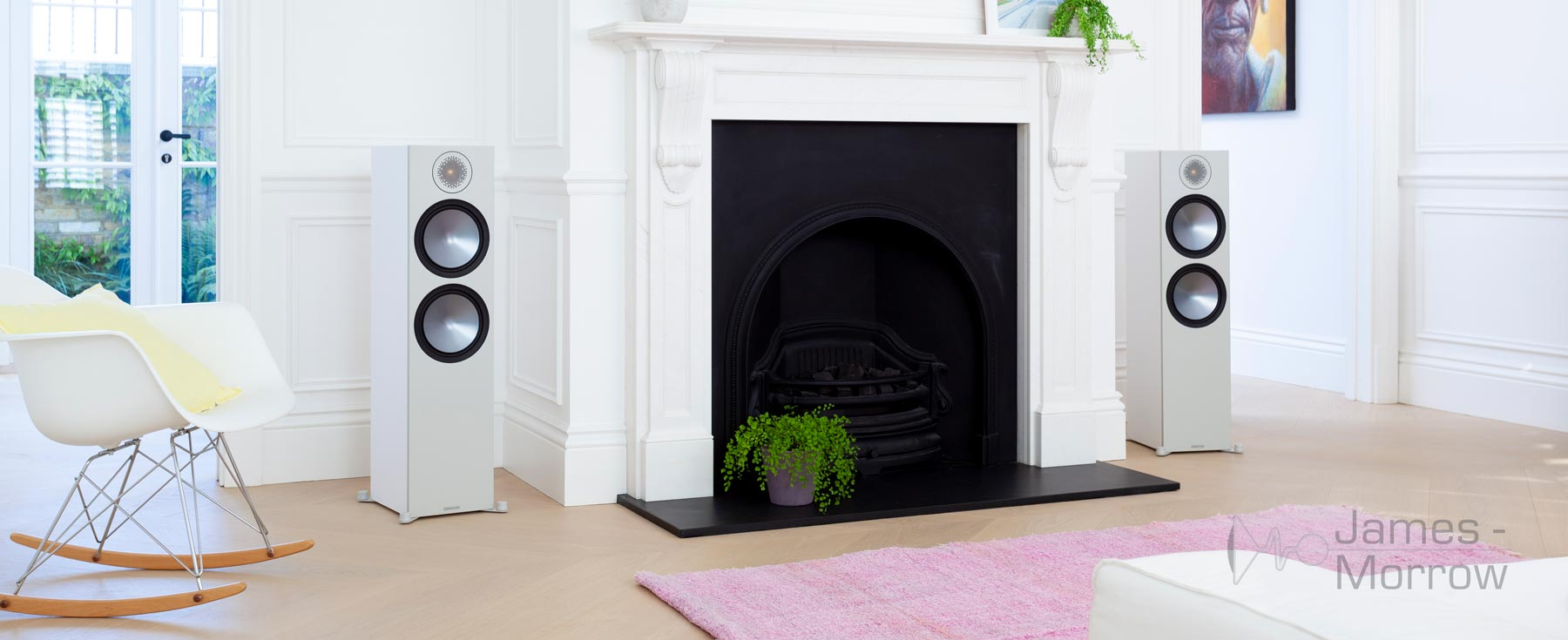 Monitor Audio Bronze 500 white pair near fireplace lifestyle image