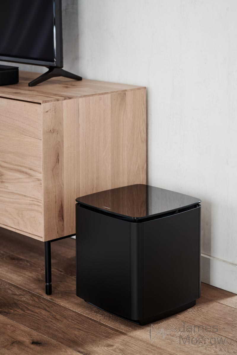 bose bass module 700 black on floor near wooden TV stand lifestyle image